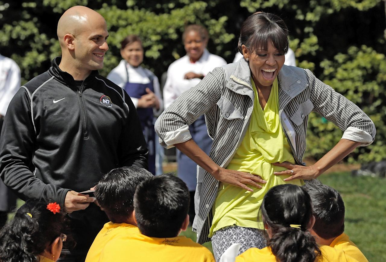 """WASHINGTON, DC - APRIL 04:  U.S. first lady Michelle Obama jokes with schoolchildren with White House chef Sam Kass (L) after planting the White House Kitchen Garden on the South Lawn of the White House April 4, 2013 in Washington, DC. For the fifth time, the first lady invited students from """"schools that have made exceptional improvements to school lunches"""" from Florida, Massachusetts, Tennessee and Vermont to help her plant the garden.  (Photo by Win McNamee/Getty Images)"""