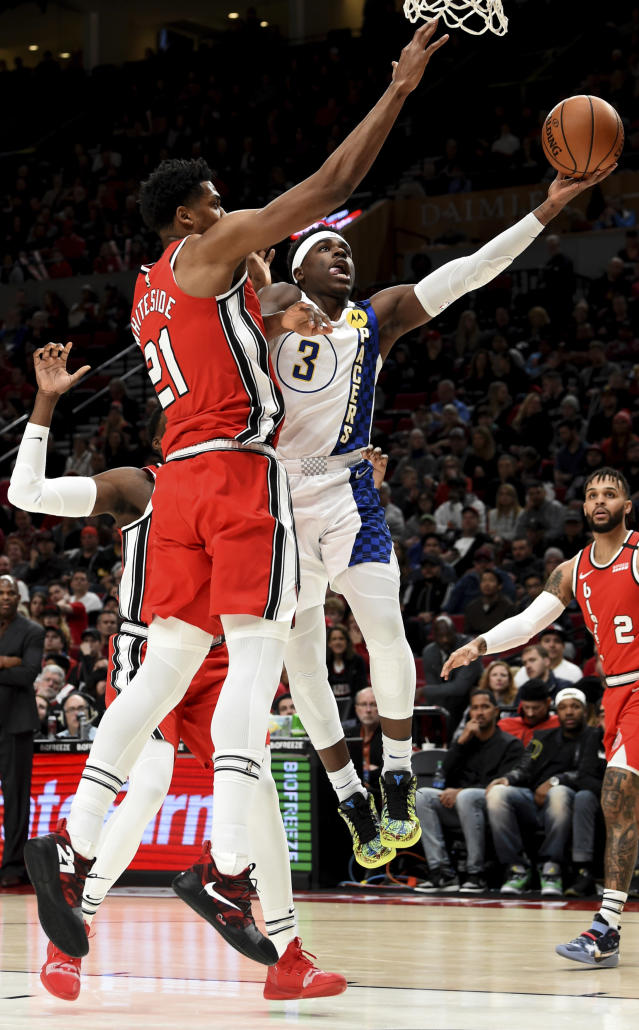 Indiana Pacers guard Aaron Holiday, right, drives to the basket on Portland Trail Blazers center Hassan Whiteside, left, during the first half of an NBA basketball game in Portland, Ore., Sunday, Jan. 26, 2020. (AP Photo/Steve Dykes)