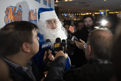New York Mets outfielder Brandon Nimmo, dressed as Santa, speaks to reporters during the team's annual Kids Holiday Party, Wednesday, Dec. 4, 2019, in New York. (AP Photo/Mary Altaffer)