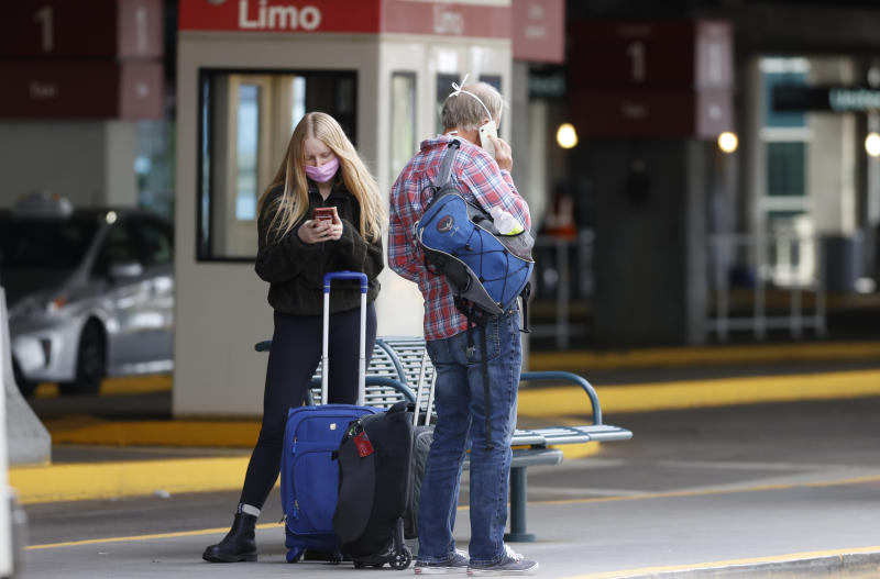 Travelers in face masks ait for a shuttle bus outside the main terminal after arriving at Denver International Airport Thursday, April 23, 2020, in Denver. (AP Photo/David Zalubowski)