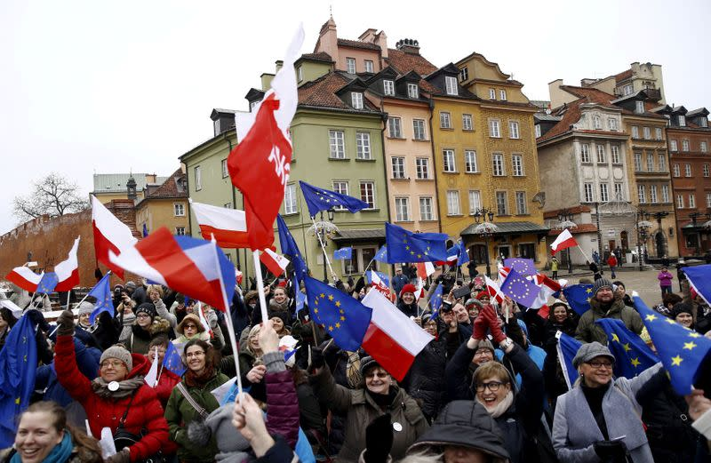 FILE PHOTO: People hold EU and Polish flags as they gather during a pro-democracy demonstration at the Old Town in Warsaw