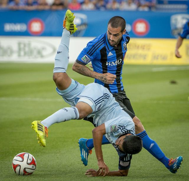 Sporting Kansas City's Igor Juliao flips through the air as Montreal Impact's Andres Romero looks on during the first half of a soccer game, Saturday, July 12, 2014 in Montreal. (AP Photo/The Canadian Press, Peter McCabe)