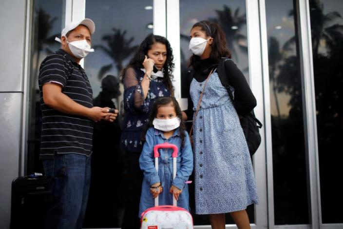 A family of travelers react after El Salvador's President Bukele ordered the closing of the airport in San Luis Talpa