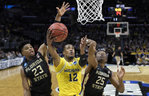 Michigan guard Muhammad-Ali Abdur-Rahkman (12) shoots between Florida State guard M.J. Walker (23) and forward Mfiondu Kabengele (25) during the first half of an NCAA men's college basketball tournament regional final Saturday, March 24, 2018, in Los Angeles. (AP Photo/Jae Hong)