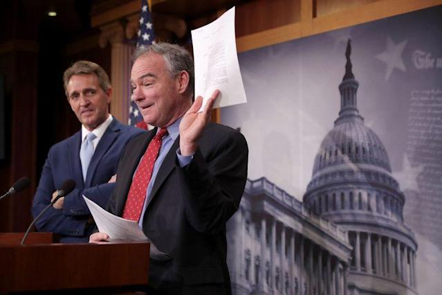 Sen. Tim Kaine, center, and Sen. Jeff Flake talk about their introduction of a new Authorization for the Use of Military Force against ISIS. (Photo: Chip Somodevilla/Getty Images)