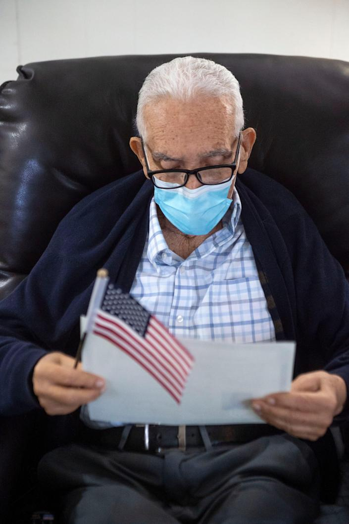 After passing his citizenship test several days prior and shortly after being sworn in as a U.S. citizen, Felix Taborda Romero reads over his Certificate of Naturalization on Monday at his home in Martin County, Florida.