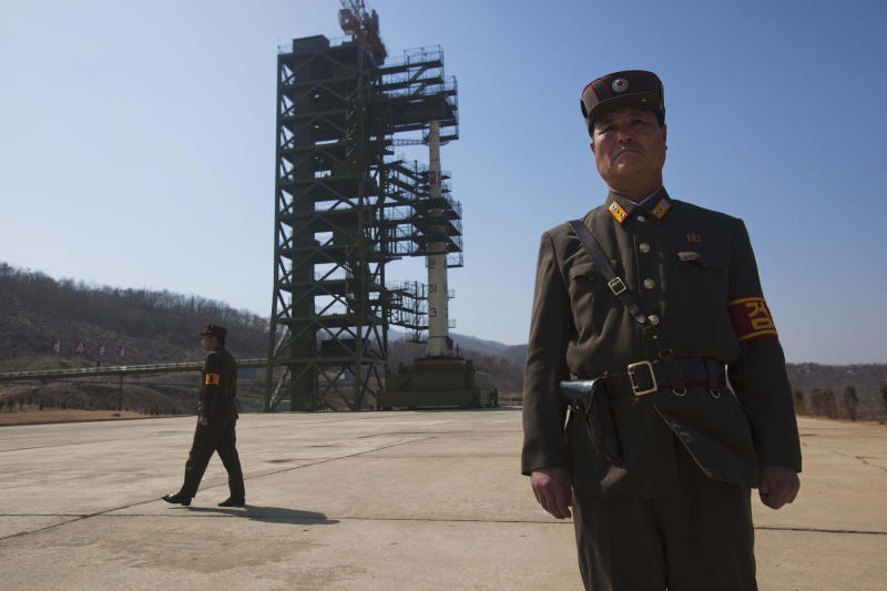 North Korean soldiers stands in front of the country's Unha-3 rocket, slated for liftoff between April 12-16, at Sohae Satellite Station in Tongchang-ri, North Korea on Sunday April 8, 2012. North Korean space officials have moved a long-range rocket into position for this week's controversial satellite launch, vowing Sunday to push ahead with their plans in defiance of international warnings against violating a ban on missile activity. (AP Photo/David Guttenfelder)