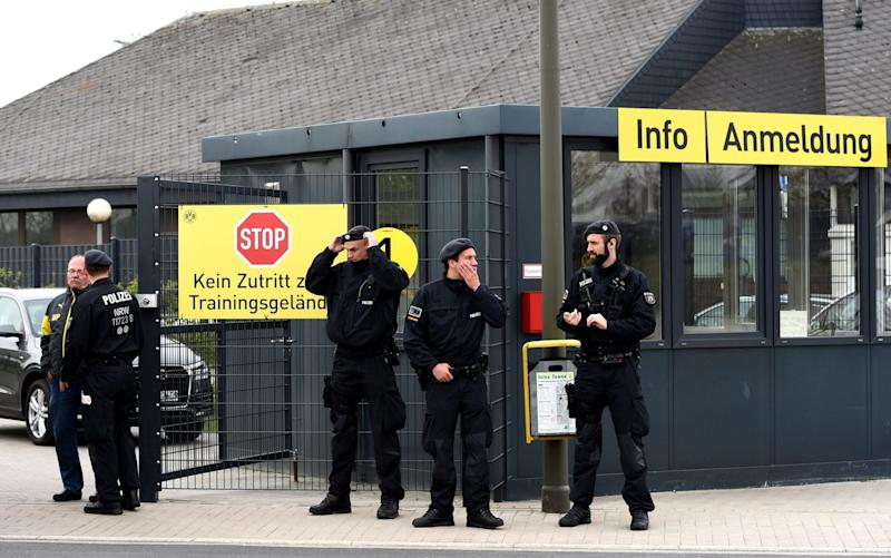 Policemen stand in front of the main entrance of the Dortmund training ground in Brackel  - Credit: PATRIK STOLLARZ/AFP