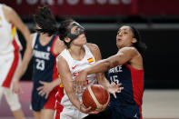 Spain's Cristina Ouvina is fouled by France's Gabrielle Williams (15) while driving to the basket during a women's basketball quarterfinal round game at the 2020 Summer Olympics, Wednesday, Aug. 4, 2021, in Saitama, Japan. (AP Photo/Charlie Neibergall)