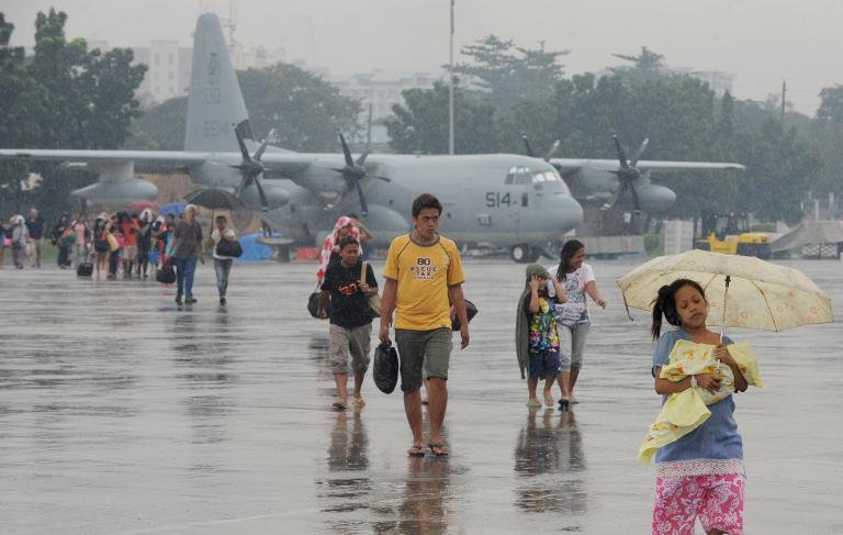 People who survived the wrath of Super Typhoon Haiyan in the central coastal city of Tacloban disembark from a US KC-130 military cargo plane that flew them out of the city to Manila on November 13, 2013