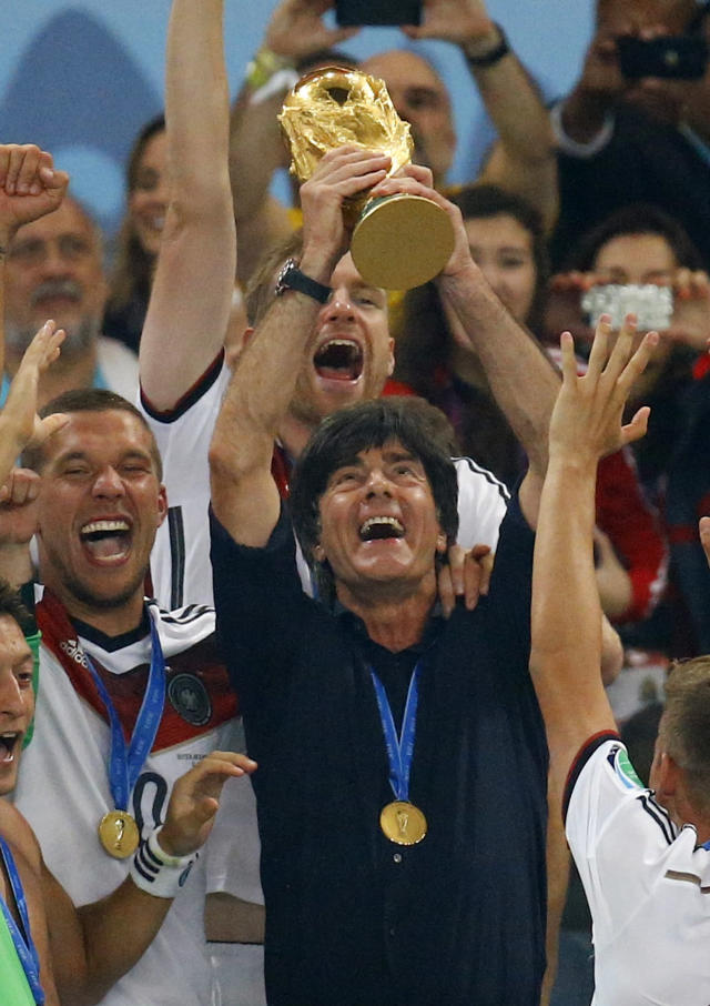 Germany's coach Joachim Loew lifts the World Cup trophy next to Lukas Podolski (L) after the 2014 World Cup final between Germany and Argentina at the Maracana stadium in Rio de Janeiro July 13, 2014. REUTERS/Kai Pfaffenbach (BRAZIL - Tags: SPORT SOCCER WORLD CUP TPX IMAGES OF THE DAY)