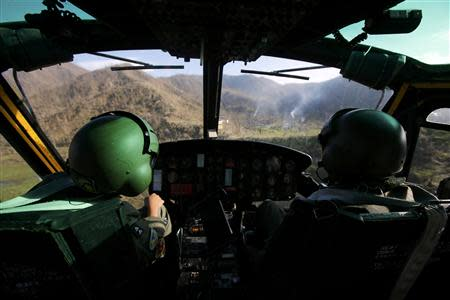 Smoke rises from campfires as a helicopter crew of the Philippine Air Force approaches a mountainous area inaccessible for vehicles, to distribute food, some 25km (17 miles) west of Tacloban city November 17, 2013. The Philippine and U.S. Air Forces are flying rice, clothes and drinking water into remote areas of the central Philippines, which are unreachable by vehicles. REUTERS/Wolfgang Rattay