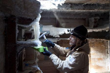 Mawson's Huts Foundation chief conservator, Dr Ian Godfrey, chips ice from the shelves in Sir Douglas Mawson's bedroom in Mawson's Hut at Cape Denison in Antarctica in this December 11, 2015 handout photo. REUTERS/David Killick/Mawsons Huts Foundation/Handout via Reuters