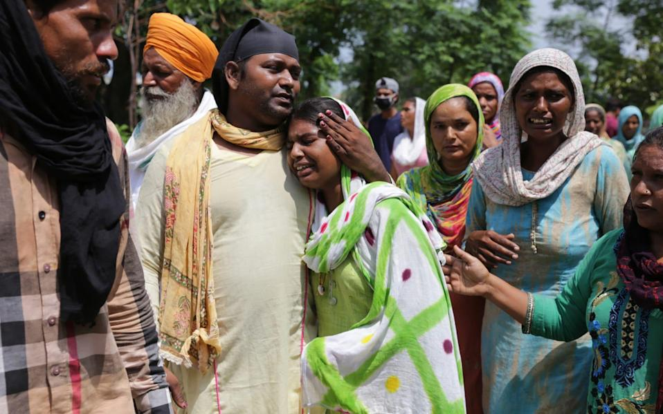 Relatives at the funeral of Karpal Singh, who died after allegedly consuming the alcohol in Punjab - EPA