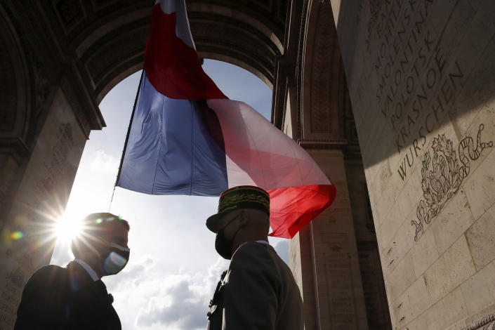 French President Emmanuel Macron, left, talks to Gen. Francois Lecointre during a ceremony at the Arc de Triomphe to mark the 76th anniversary of the end of World War II, in Paris, Saturday, May 8, 2021.(Christian Hartmann/Pool via AP)