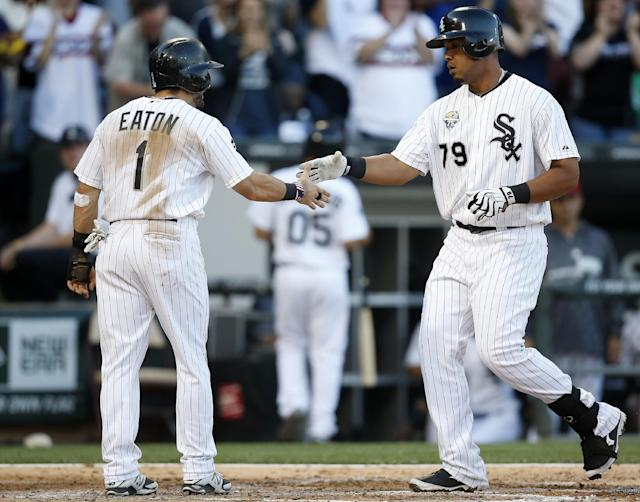 Chicago White Sox's Jose Abreu, right, celebrates his two-run home run with teammate Adam Eaton, left, who also scored, against the Seattle Mariners during the fifth inning of a baseball game on Friday, July 4, 2014, in Chicago. (AP Photo/Andrew A. Nelles)