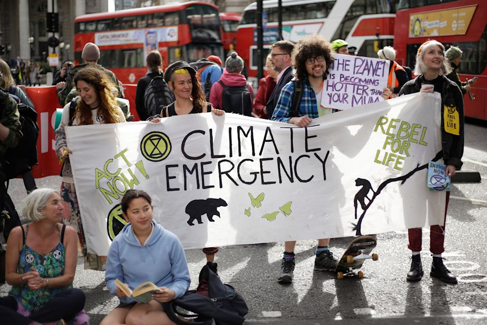 Extinction Rebellion climate change protesters briefly block the road in the City of London, Thursday, April 25, 2019. The non-violent protest group, Extinction Rebellion, is seeking negotiations with the government on its demand to make slowing climate change a top priority. (AP Photo/Matt Dunham)
