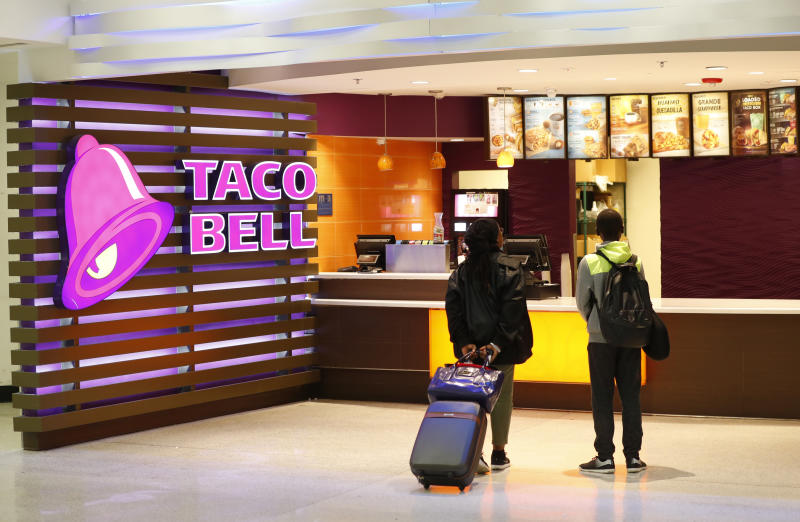 In this Friday, April 19, 2019 photo, travelers look at a menu at a Taco Bell restaurant inside Miami International Airport in Miami. Yum Brands, which operates Taco Bell, reports financial results Wednesday, May 1. (AP Photo/Wilfredo Lee)