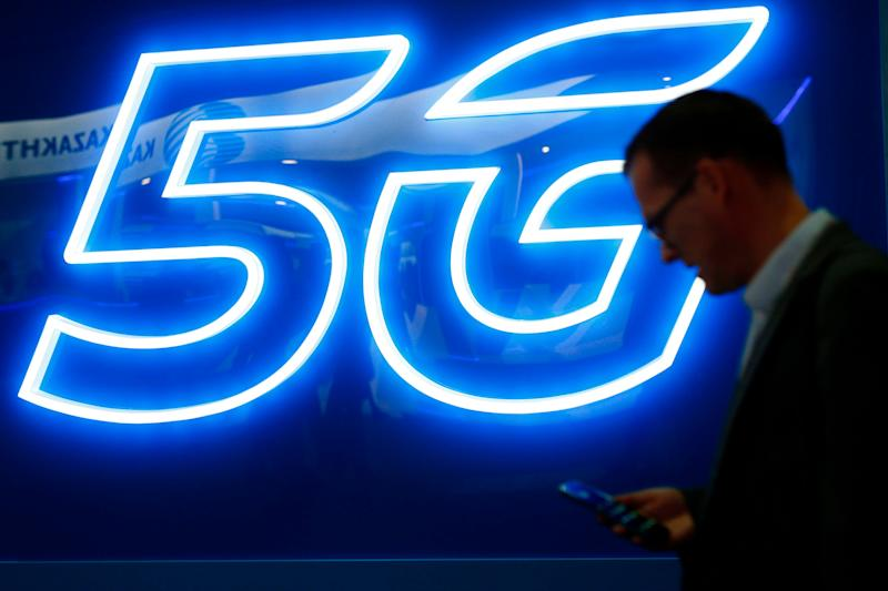 A man uses his phone next to a 5G hotspot sign at the Mobile World Congress (MWC) in Barcelona on February 26, 2019. - Phone makers will focus on foldable screens and the introduction of blazing fast 5G wireless networks at the world's biggest mobile fair as they try to reverse a decline in sales of smartphones. (Photo by Pau Barrena / AFP) (Photo credit should read PAU BARRENA/AFP/Getty Images)