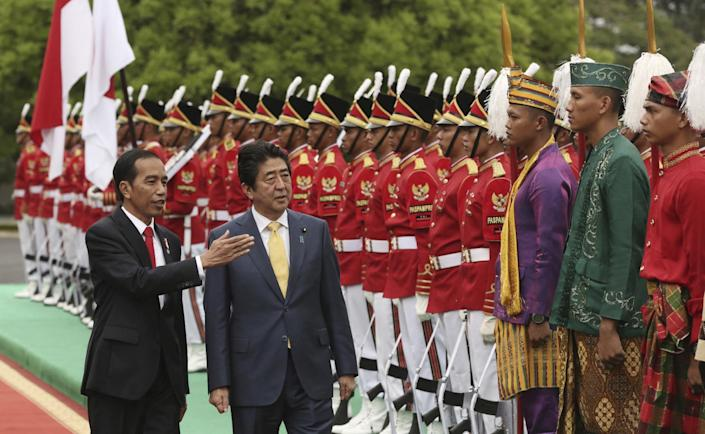 FILE - In this Jan. 15, 2017 file photo, Indonesia President Joko Widodo, left, talks to Japan's Prime Minister Shinzo Abe as Abe inspects an honor guard during a welcome ceremony at Presidential Palace in Bogor, West Java, during Abe's visit to Indonesia. China is not happy with Abe's high-profile visits to the Philippines, Australia, Indonesia and Vietnam over concerns that he may be trying to pull the rug under Beijing's efforts to pacify its neighbors in and around the South China Sea. (AP Photo/Achmad Ibrahim, File)