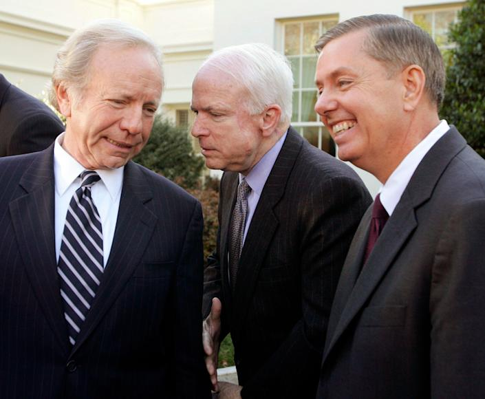 """McCain confers with Sens. Joe Lieberman (D-Conn.) and Lindsey Graham (R-S.C.) during remarks to the press outside the West Wing of the White House in Washington on Dec. 16, 2005. The senators were often referred to as the """"three amigos."""""""