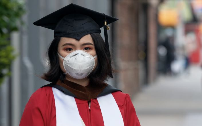 A student wearing a mask, gloves, graduation cap, and gown poses amid the coronavirus pandemic on May 14, 2020 in New York City. (Photo: Alexi Rosenfeld/Getty Images)