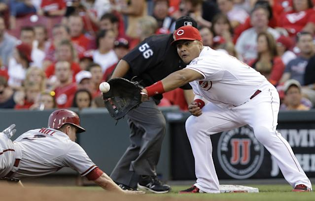 Arizona Diamondbacks' Aaron Hill (2) dives safely back to first base as Cincinnati Reds first baseman Brayan Pena catches a pickoff throw from starting pitcher Mike Leake in the fourth inning of a baseball game, Tuesday, July 29, 2014, in Cincinnati. (AP Photo/Al Behrman)