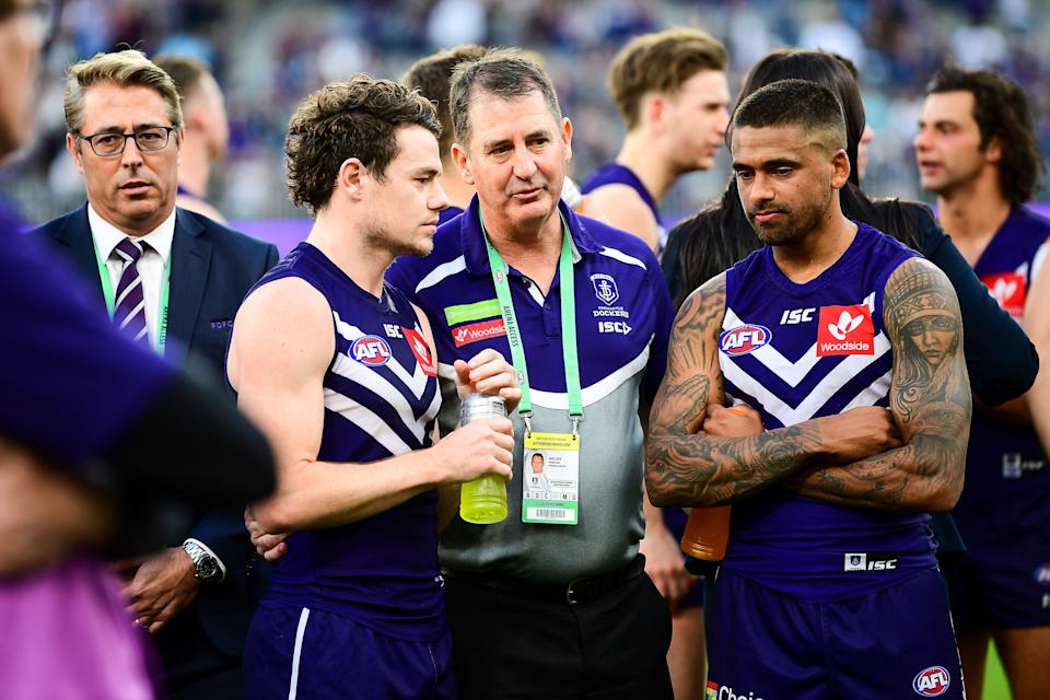 Ross Lyon (pictured middle) talks with Lachie Neale (pictured centre left) back in 2018.