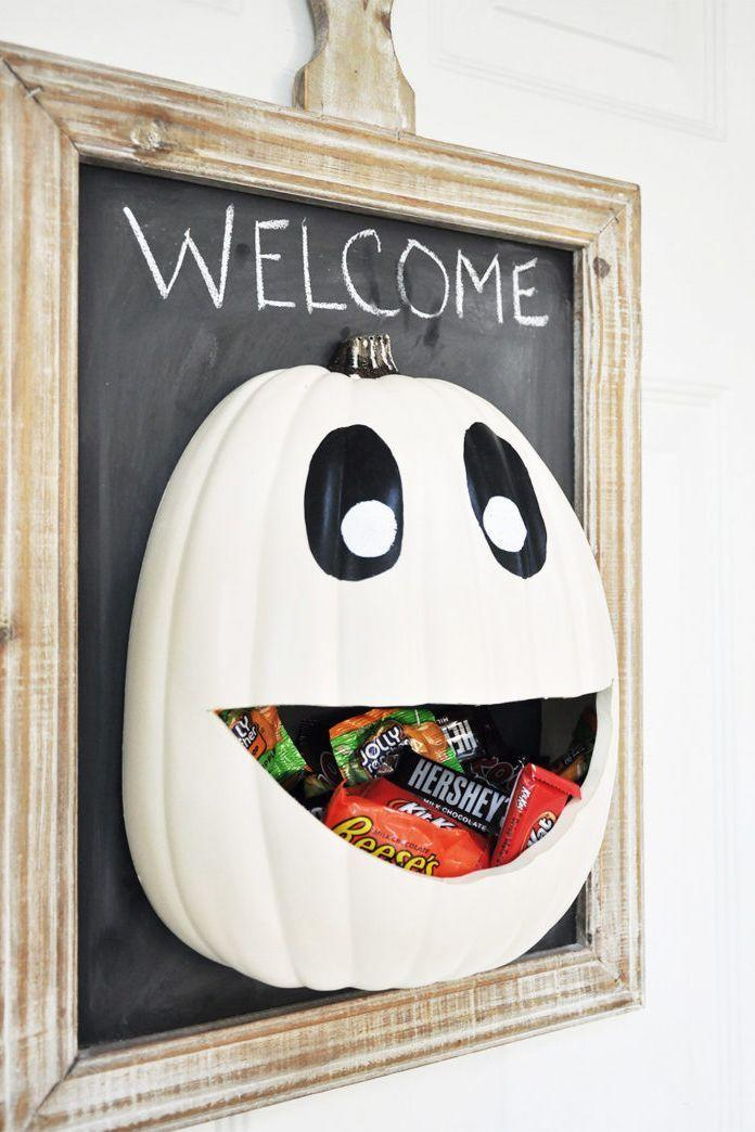 """<p>Here's a DIY that's as useful as it is fun to make. Plus, in 2020, you might appreciate that the smiling pumpkin keeps a little distance between you and your trick-or-treaters. </p><p><strong>Get the tutorial at <a href=""""https://cherishedbliss.com/diy-halloween-candy-door-hanger-recipe/"""" rel=""""nofollow noopener"""" target=""""_blank"""" data-ylk=""""slk:Cherished Bliss"""" class=""""link rapid-noclick-resp"""">Cherished Bliss</a>.</strong></p><p><strong><a class=""""link rapid-noclick-resp"""" href=""""https://go.redirectingat.com?id=74968X1596630&url=https%3A%2F%2Fwww.walmart.com%2Fip%2FRust-Oleum-Specialty-Black-Chalk-Board-Paint-30-fl-oz%2F17011098&sref=https%3A%2F%2Fwww.thepioneerwoman.com%2Fholidays-celebrations%2Fg32894423%2Foutdoor-halloween-decorations%2F"""" rel=""""nofollow noopener"""" target=""""_blank"""" data-ylk=""""slk:SHOP CHALKBOARD PAINT"""">SHOP CHALKBOARD PAINT</a><br></strong></p>"""