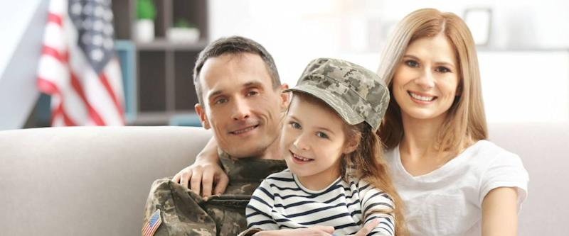 Soldier in camouflage and his family sitting on sofa at home