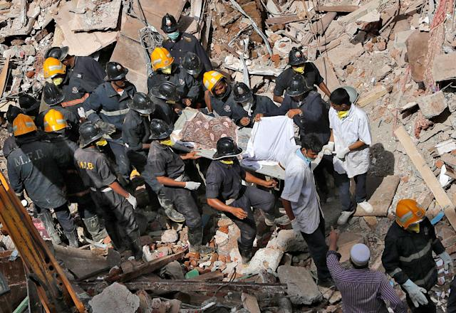 <p>Firefighters carry the body of a victim from the site of a collapsed building in Mumbai, India, August 31, 2017. (Photo: Shailesh Andrade/Reuters) </p>