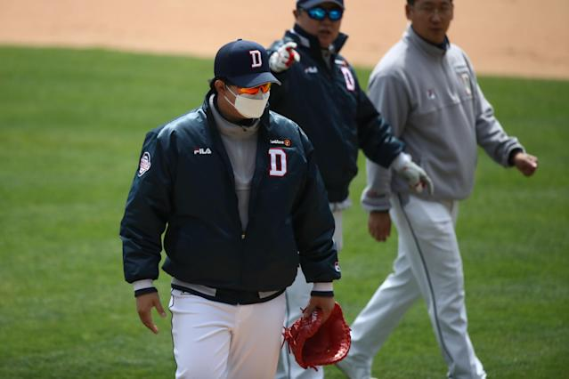 As the KBO prepares to begin its season after a coronavirus-induced delay, the league is implementing precautions in hopes of playing its full schedule. Masks will be worn by non-players, like this Doosan Bears staffer prior to a preseason game. (Photo by Chung Sung-Jun/Getty Images)