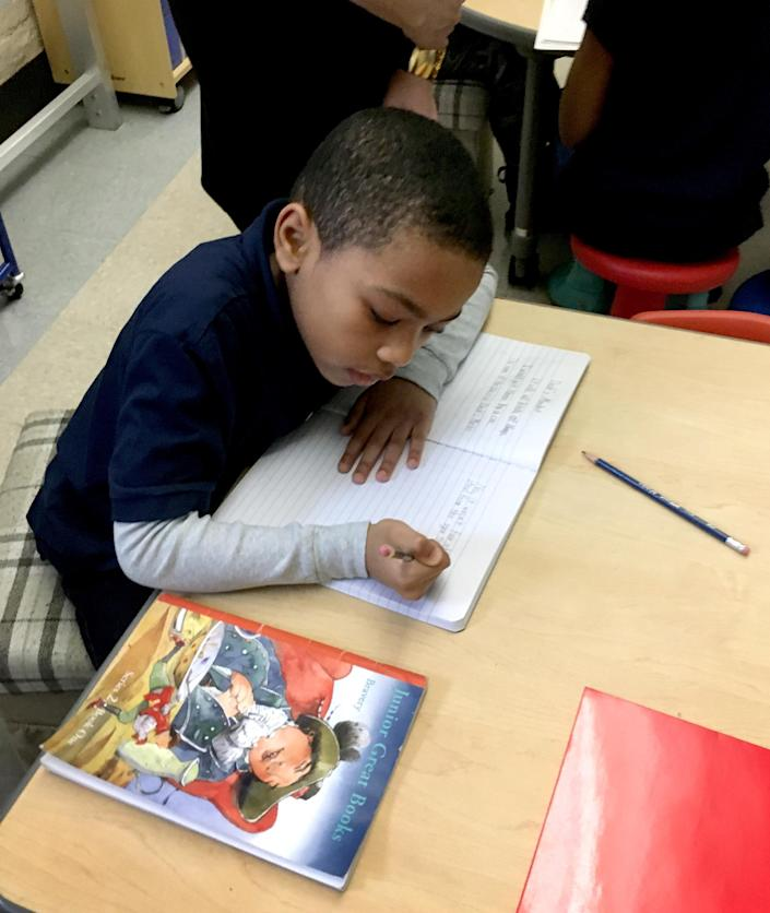 Image: Howard Thompson III writes in the Eve #61 gifted and talented class. His father hoped to move him to the more-established gifted program at Olmsted #64. (Danielle Dreilinger for The Hechinger Report)