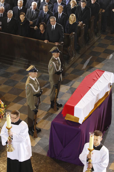 The wooden coffin of Poland's and Eastern Europe's first post-communist prime minister, Tadeusz Mazowiecki, covered with Poland's national white-and-red flag lying in state at St. John's Cathedral during a funeral Mass in Warsaw, Poland, on Sunday, Nov. 3, 2013. Mazowiecki died at a Warsaw hospital on Monday, aged 86. (AP Photo/Czarek Sokolowski)
