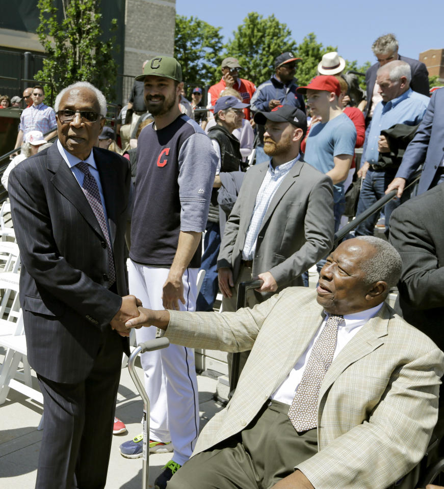 Frank Robinson, left, greets Hank Aaron before a baseball game between the Kansas City Royals and the Cleveland Indians, Saturday, May 27, 2017, in Cleveland. Robinson was MLB's first African-American manager. He became a player-manager for the Indians in 1975. (AP Photo/Tony Dejak)