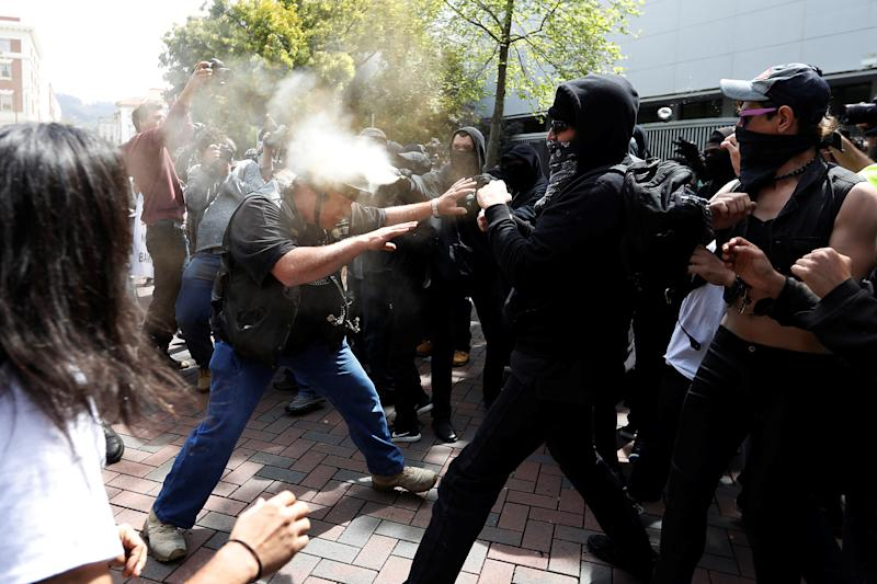 A man in support of U.S. President Donald Trump (L) is being pepper spray by a group on counter-protestor during a rally in Berkeley, California in Berkeley, California, U.S., April 15, 2017. REUTERS/Stephen Lam