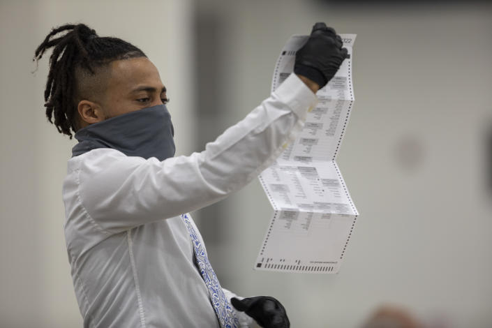 A worker with the Detroit Department of Elections inspects an absentee ballot at the Central Counting Board in the TCF Center on November 4, 2020 in Detroit, Michigan. (Elaine Cromie/Getty Images)