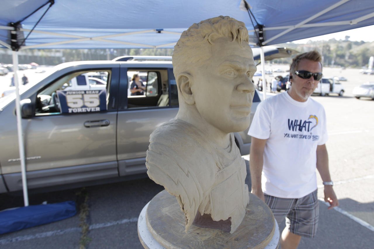 Mark Martensen, right, stands next to a sculpture he made of late football player Junior Seau while waiting for a public memorial service for Seau at Qualcomm Stadium Friday, May 11, 2012, in San Diego. Seau committed suicide on May 2 at his Oceanside, Calif., home. He played parts of 20 seasons in the NFL, with the San Diego Chargers, Miami Dolphins and New England Patriots. (AP Photo/ Gregory Bull)