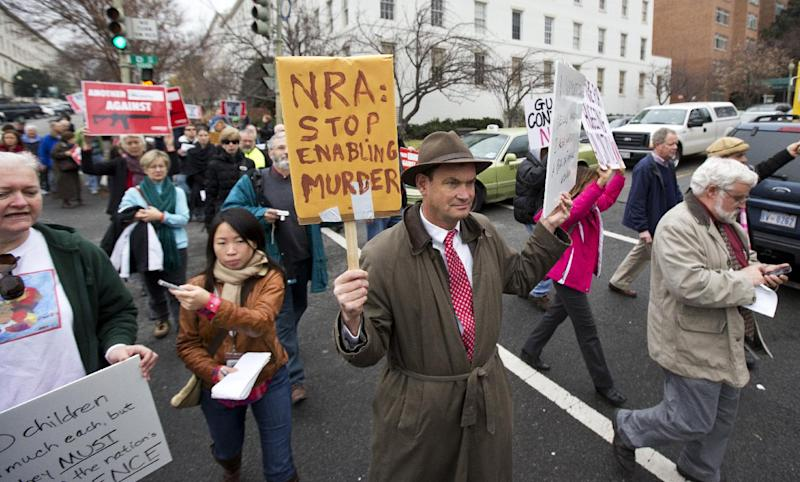 Patrick Hand, center, joins a march to the National Rifle Association headquarters on Capitol Hill in Washington Monday, Dec. 17, 2012. Curbing gun violence will be a top priority of President Barack Obama's second term, aides say. but exactly what he'll pursue and how quickly are still evolving. (AP Photo/Manuel Balce Ceneta)