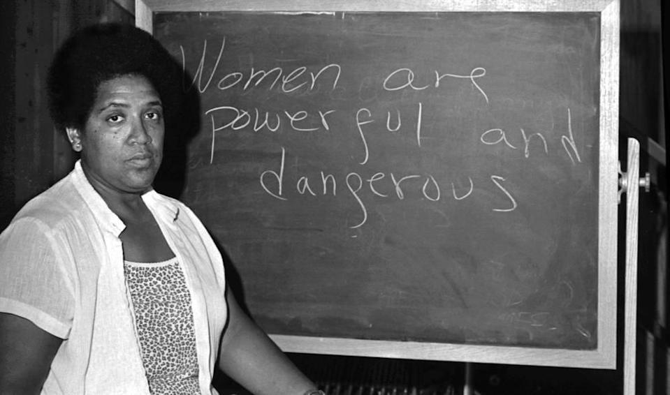 Audrey Lorde standing in front of a chalkboard with the message 'women are powerful and dangerous'