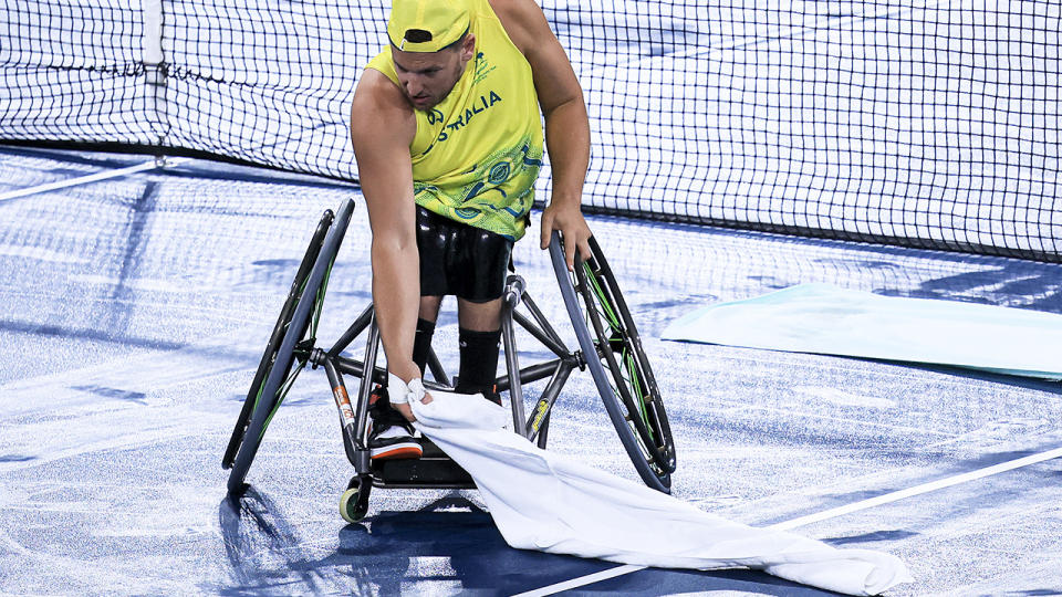 Dylan Alcott, pictured here helping to dry the court during the quad doubles gold medal match.