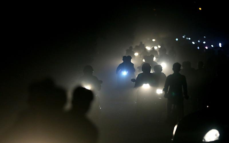 In this 2017 file photo, motorists ride through a thick blanket of smog and dust on the outskirts of New Delhi, India, with microscopic particles spiking at times to 75 times the level considered safe by the World Health Organization. According to a scientific report from the United Nations released on Wednesday, March 13, 2019, the planet is becoming an increasing unhealthy place for people.