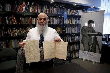 Roni Gross, curator of the Hebrew University's Albert Einstein Archive, displays original documents related to Albert Einstein's hypothesis of the existence of gravitational waves during a news conference in Jerusalem February 11, 2016. REUTERS/Ronen Zvulun