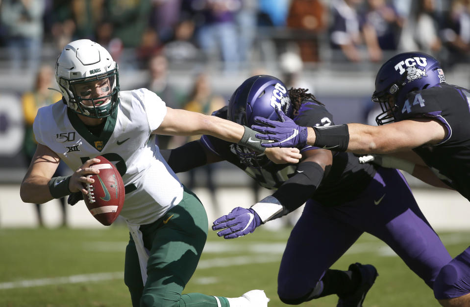 Baylor quarterback Charlie Brewer (12) tries to avoid the rush of TCU defensive ends Ochaun Mathis (32) and Colt Ellison (44) during the first half of an NCAA college football game, Saturday, Nov. 9, 2019, in Fort Worth, Texas. (AP Photo/Ron Jenkins)