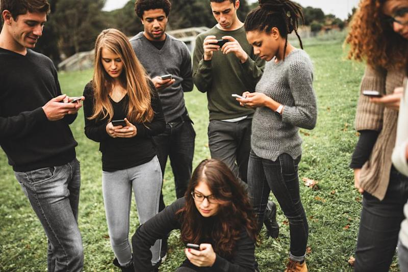 A group of young people on their phones