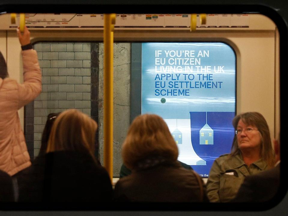 <p>A poster, aimed at EU citizens living in the UK, encourages EU nationals to apply to the Government's post-Brexit EU settlement scheme, is pictured through a carriage of a London Underground tube train, at St James's Park underground station in London</p> (AFP/Getty)