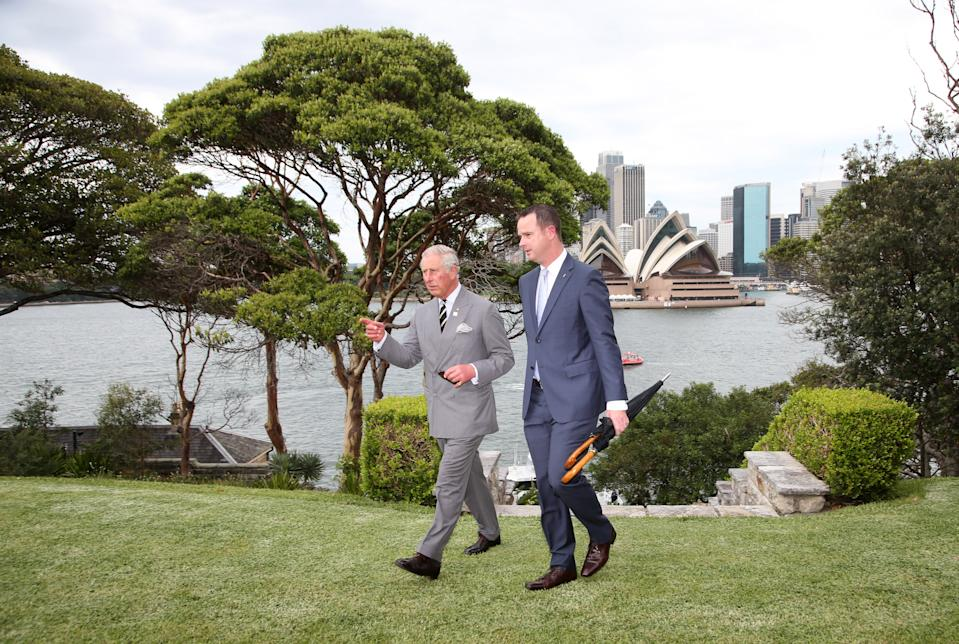 Britain's Prince Charles (L) walks along with with Paul Singer, Director of Operations for Government House, with the Sydney Opera House in the back as he arrives for a Sustainability Leadership Roundtable at Admiralty House in Sydney on November 12, 2015. 12, 2015.  Prince Charles and his wife Camilla are on a two-week tour of New Zealand and Australia.  AFP PHOTO / POOL        (Photo credit should read RICK RYCROFT/AFP via Getty Images)