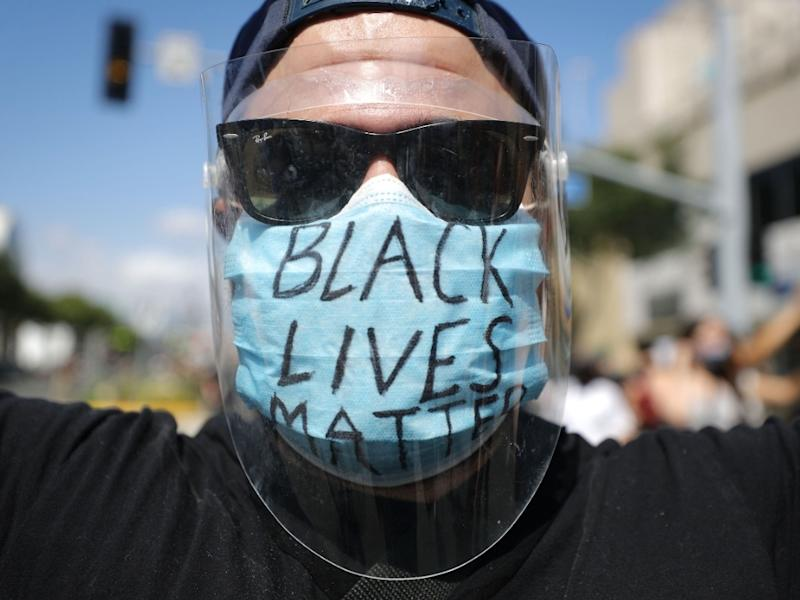 A protester wears a face mask reading 'Black Lives Matter' during a peaceful demonstration amid the COVID-19 coronavirus pandemic on June 06, 2020 in West Hollywood, California. This is the 12th day of protests since George Floyd died in Minneapolis polic