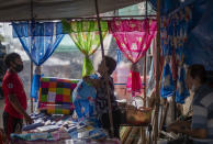 A fabric vender negotiates with a buyer at a roadside shop in Bangkok, Thailand, Wednesday, Aug. 5, 2020. Thailand has managed to curb COVID-19 infections over the last three months with strict controls on entry into the country and aggressive testing and quarantine requirements. But its economy is expected to contract by at least 5% in 2020, according to the World Bank. (AP Photo/ Gemunu Amarasinghe)
