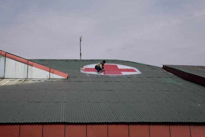A Kashmiri worker paints the red and white medical emblem of cross on the roof of SMHS hospital as tensions escalate between India and Pakistan in Srinagar, Indian controlled Kashmir, Wednesday, Feb. 27, 2019. (AP Photo/ Dar Yasin)